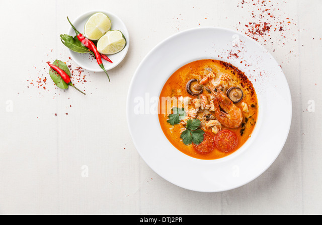 Spicy Thai soup Tom Yam with Coconut milk, Chili pepper and Seafood - Stock Image