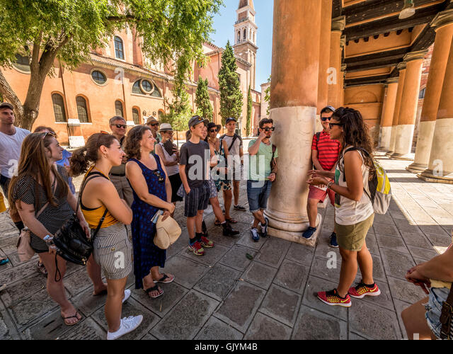 Tour guide addressing a group of tourists on a sustainable tourism walking tour of Venice, Italy. - Stock Image