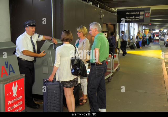 Boston Massachusetts Logan International Airport BOS curbside check-in American Airlines skycap explaining man woman - Stock Image