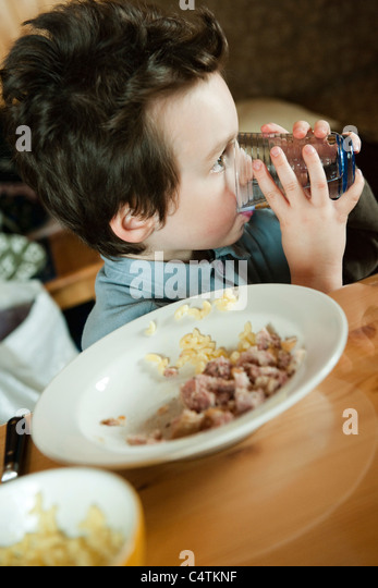 Little boy at table, drinking glass of water - Stock-Bilder