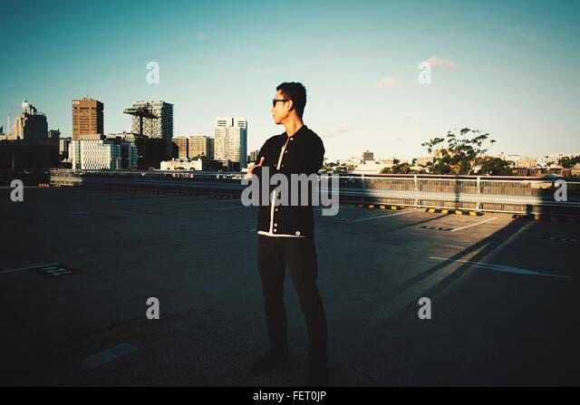 Young Man Standing On Street Against Sky - Stock Image
