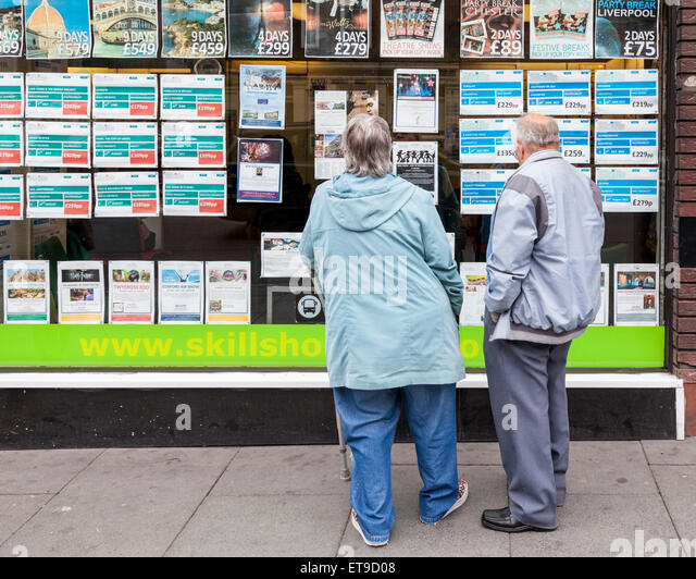 Older couple looking at holiday information in a travel agent's window, Skills Holidays, Nottingham, England, - Stock-Bilder