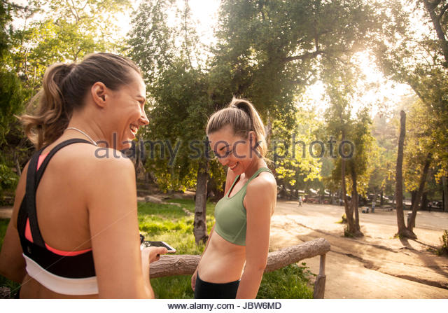 Two young women outdoors, wearing sports clothing, looking at smartphone - Stock-Bilder