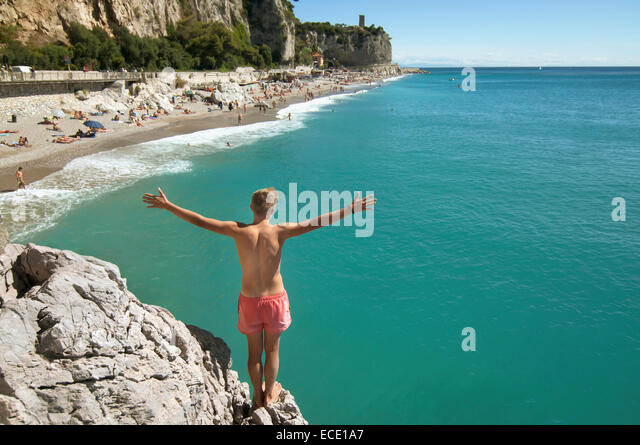Teenager boy cliff holiday ocean waiting adventure - Stock Image