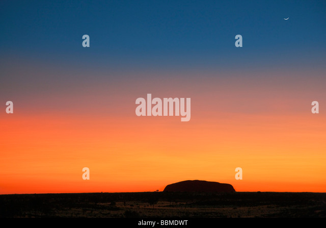 Australia, Northern Territory. Before sunrise, Uluru or Ayres Rock is silhouetted against a magnificent blood red - Stock Image