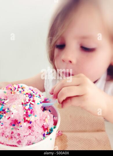 A little girl enjoys a frozen treat with sprinkles on top - Stock Image