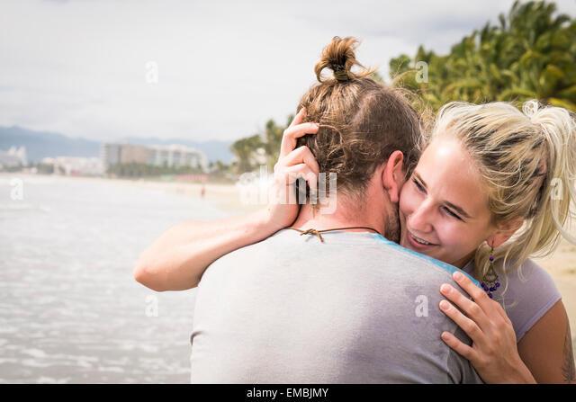 Young woman hugging young man, smiling, at a beach. Riviera Nayarit, Pacific Coast, Mexico - Stock Image