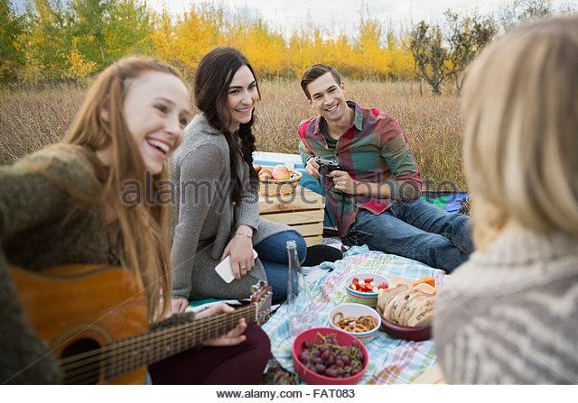 Friends enjoying picnic in field - Stock Image