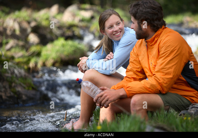 Backpacking couple take a break by a stream - Stock Image