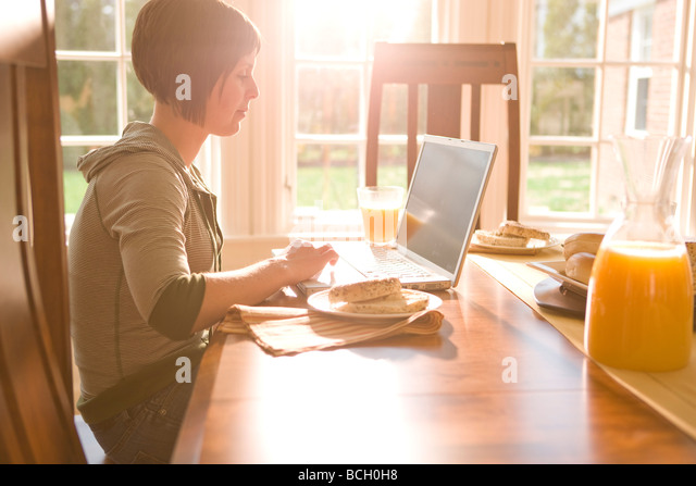 Young woman using her laptop at breakfast - Stock-Bilder