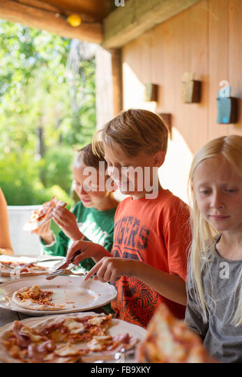 Sweden, Skane, Brothers (8-9) and sister (10-11) eating pizza at family dinner - Stock-Bilder