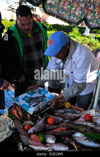 Fishmonger with selected fish from the nearby Essaouira  port , for grilling a the outside fish eateries  at   Essaouira - Stock Image