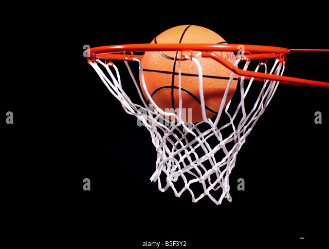 Basketball in hoop on black background - Stock Image