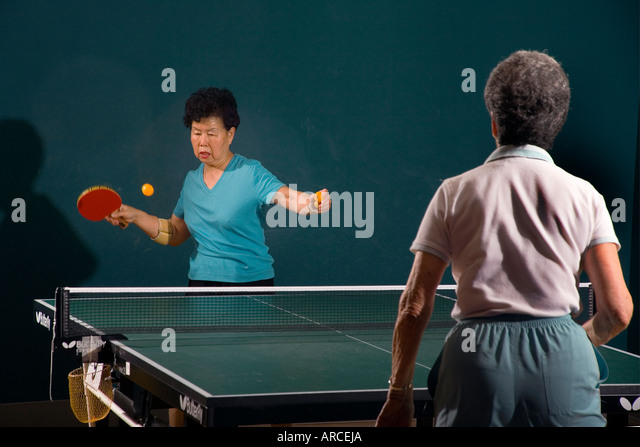 Two women over age 70 play ping pong at a seniors athletic facility - Stock Image
