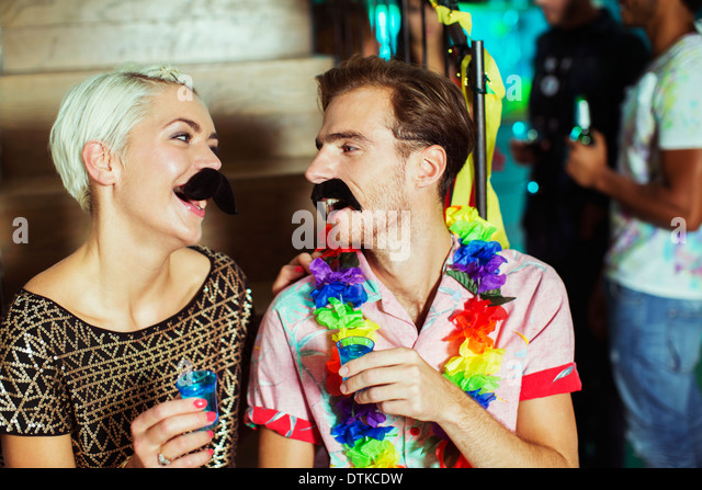 Couple wearing fake mustaches at party - Stock Image
