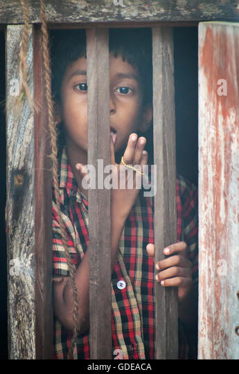 Unidentified Indian boy looks through a window at home in small fishing village - Stock Image