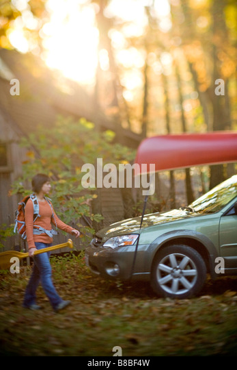 Woman walking with canoe paddles in front of cabin in the woods - Stock Image