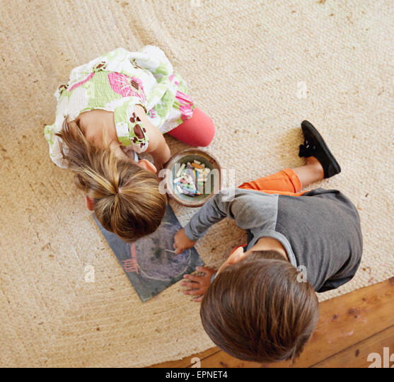 Top view of two little kids sitting on floor drawing with color chalks. - Stock-Bilder