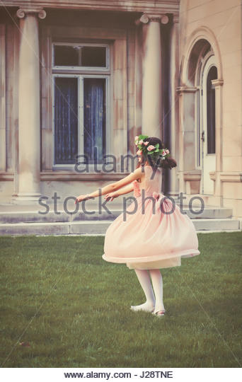 Young girl twirling and playing in the garden - Stock Image