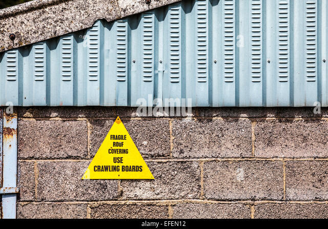 A notice warning about a fragile roof. - Stock Image