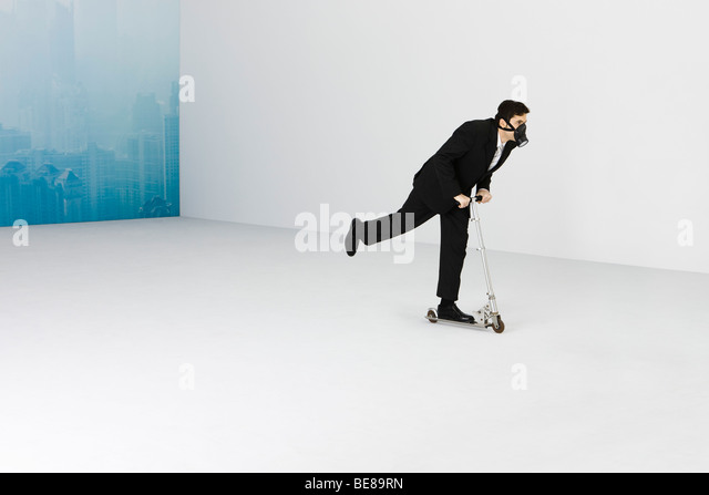 Businessman wearing gas mask riding push scooter, cityscape obscured by smog in background - Stock Image