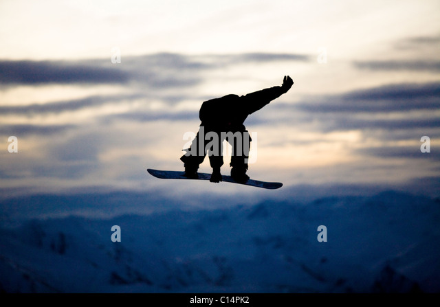 A male snowboarder does a backside 180 mute grab while riding at a snow park in Wanaka, New Zealand. - Stock Image