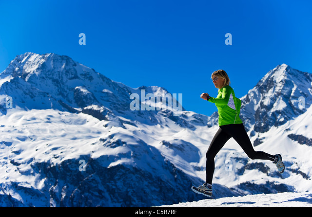 A women jogging across snowy alpine mountains. - Stock-Bilder