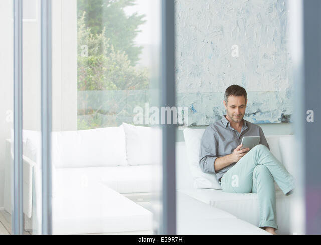 Man using digital tablet on sofa - Stock Image