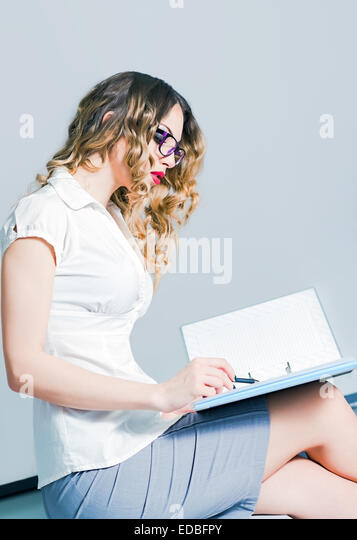 A beautiful young business woman working with documents - Stock-Bilder