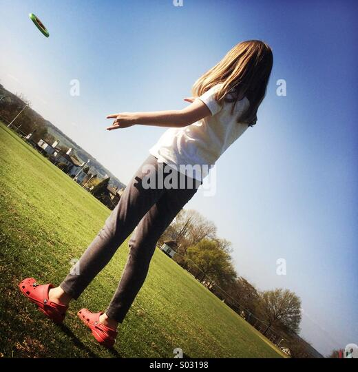 Girl Throwing A Frisbee - Stock Image