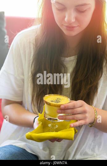 teenage girl holding a glass of mango lassi - Stock Image
