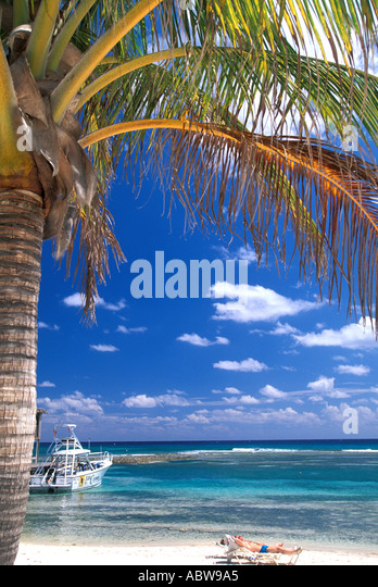 Caribbean Cayman Islands Cayman Brac beach boats palm tree clear water and blue sky man in lounge chair relaxing - Stock Image
