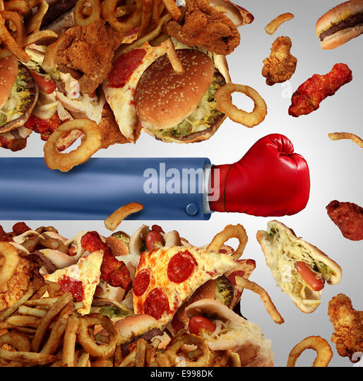 Fitness diet fight concept as a group of unhealthy junk food as hamburgers and fried fast foods being punched open - Stock-Bilder