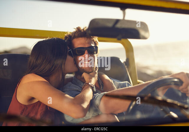 Loving young couple on road trip. Woman kissing her boyfriend's cheeks. Young man driving a car. Romantic young - Stock Image