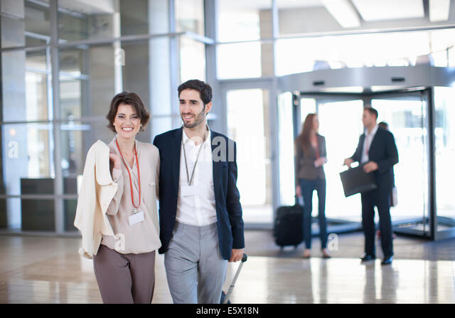 Young businessman and businesswoman arriving at conference centre - Stock Image