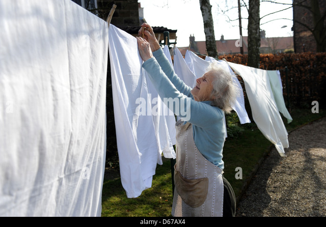 Elderly pensioner hanging out a line of washing on her washing line in April. - Stock-Bilder