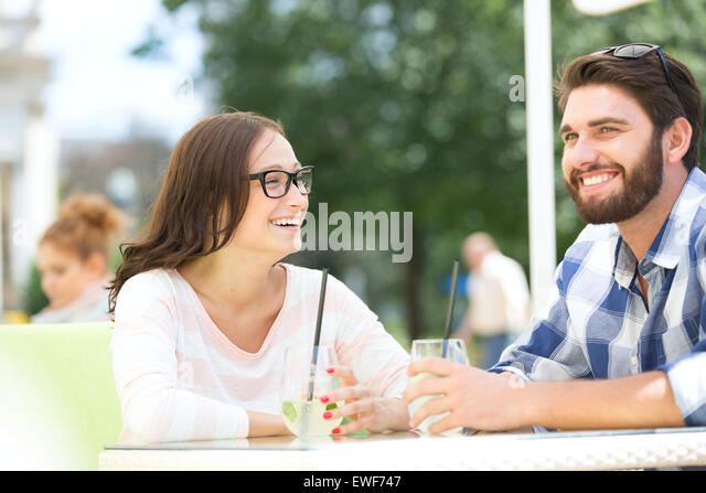 Cheerful couple having mojito at sidewalk cafe - Stock Image