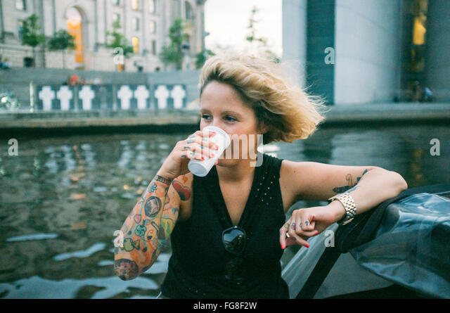 Women Sitting And Drinking On Boat At River - Stock Image