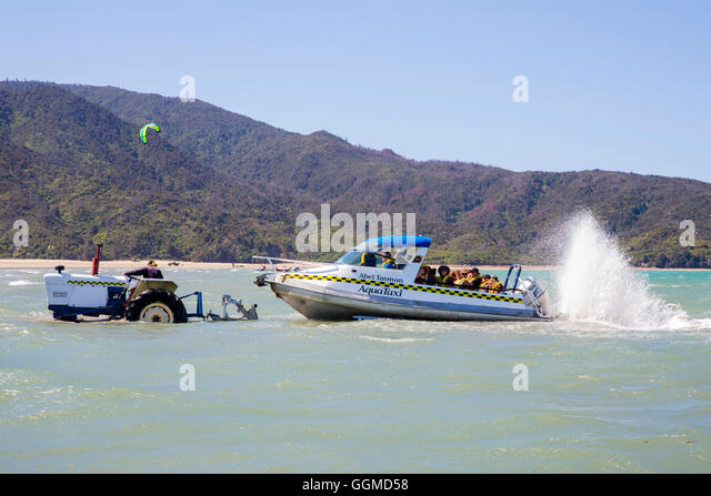 Taxiboat being tugged out at low tide out of the sea by tractors, Abel Tasman National Park, South Island, New Zealand - Stock Image