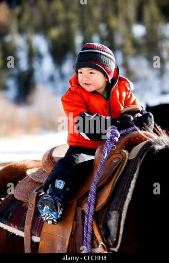 a little boy rides a horse while bundled up in a warm jacket and stocking cap / hat on a cold winter day with snow - Stock Image