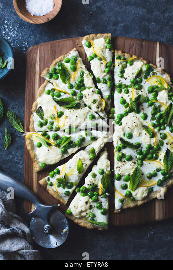 Thin and crisp grilled gluten-free pizza crust (whole grain + gluten-free) and a springy topping of fresh peas, - Stock Image