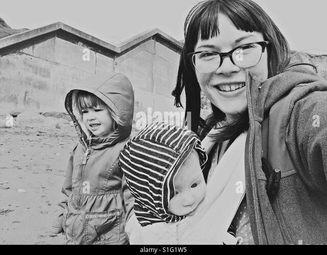 Mom and little children at beach baby wearing toddler - Stock-Bilder