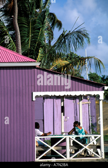 British Virgin Islands Tortola two women sitting on the porch of colorful house - Stock Image