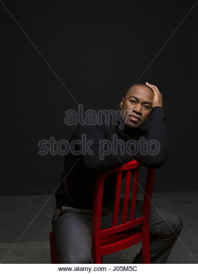 Portrait confident African American man straddling chair against black background - Stock Image