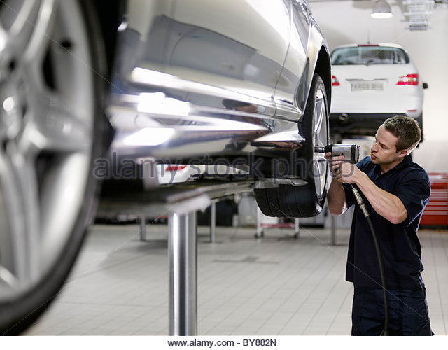 Mechanic working on car in auto repair shop - Stock Image