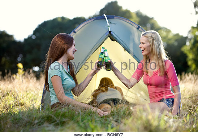 Three young women camping, two drinking beers - Stock-Bilder