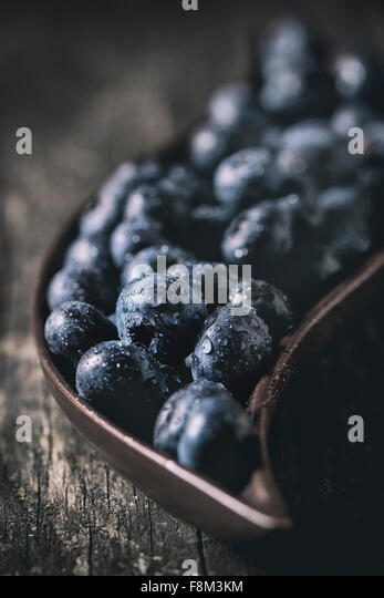 Close up of fresh wet blueberries in decorative ceramic plate over old wooden table. With retro filter effect - Stock Image