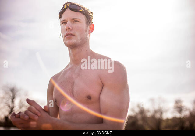 A young man in swimming trunks next to spring fresh water ponds. - Stock-Bilder