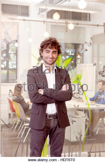 Portrait of young businessman with arms crossed. - Stock Image