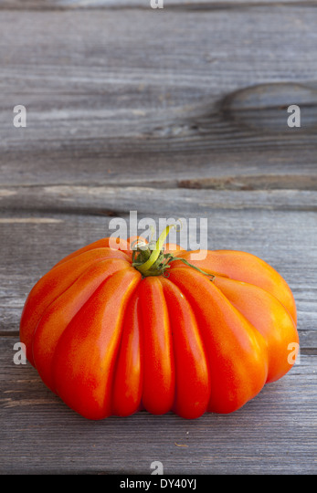 One large Beefsteak Tomato fresh from the Weekly Market on a old wooden Table - Stock Image